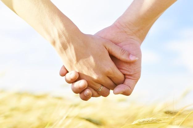 Paar hand in hand tegen de achtergrond van een gouden veld en een blauwe bewolkte hemel.
