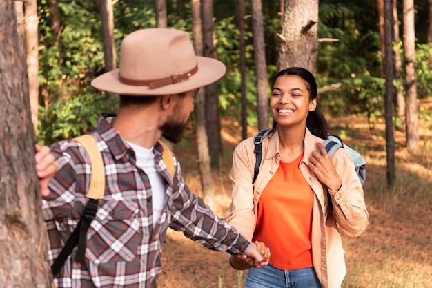 Paar hand in hand tijdens het wandelen in een bos