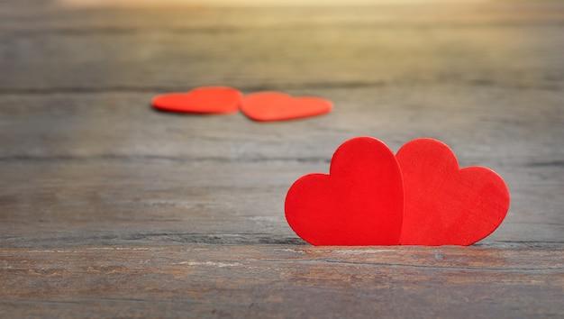 Paar harten op houten achtergrond. rode harten zijn samen in een gebarsten houten oppervlak.