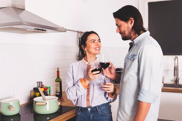 Paar het drinken wijn in keuken