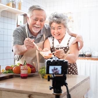 Paar het hogere aziatische oudere gelukkige leven in huiskeuken. opa afvegen grootmoeder mond na het eten van brood met jam vlog vdo voor sociale blogger. focus op camera. moderne levensstijl en relaties