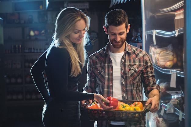Paar het kopen groenten in organische winkel
