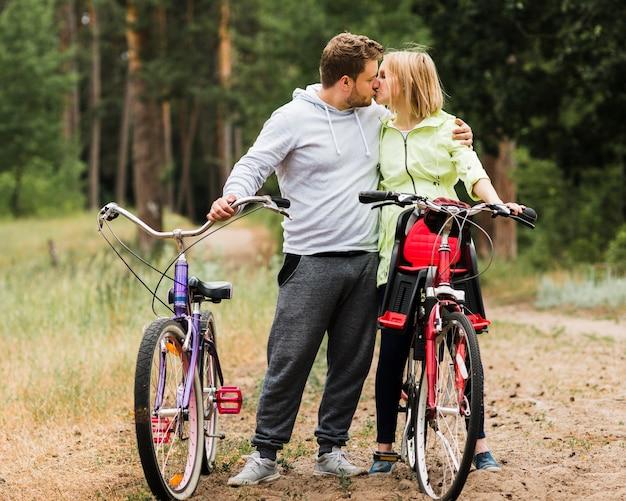 Paar het kussen naast fietsen op bosweg