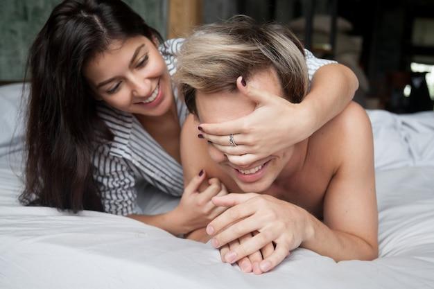 Paar het spelen in bed, ogen van de vrouwen de sluitende man met handen