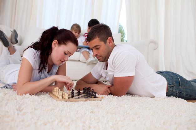 Paar het spelen schaak op vloer in woonkamer