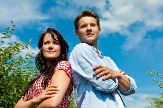 Paar het stellen in fruitboomgaard die in de afstand kijken