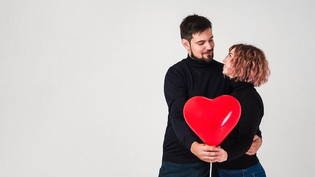 Paar het stellen met ballon voor valentijnskaarten en exemplaarruimte