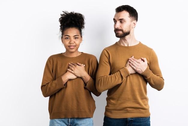 Paar het stellen met handen bij harten