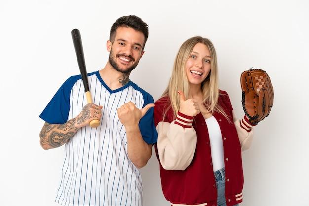 Paar honkbal spelen over geïsoleerde witte achtergrond geven een duim omhoog gebaar met beide handen en glimlachen