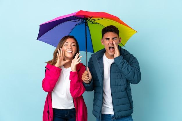 Paar houden een paraplu op blauw schreeuwen en iets aankondigen