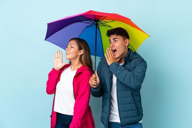 Paar houden een paraplu op blauw schreeuwen met mond wijd open naar de zijkant