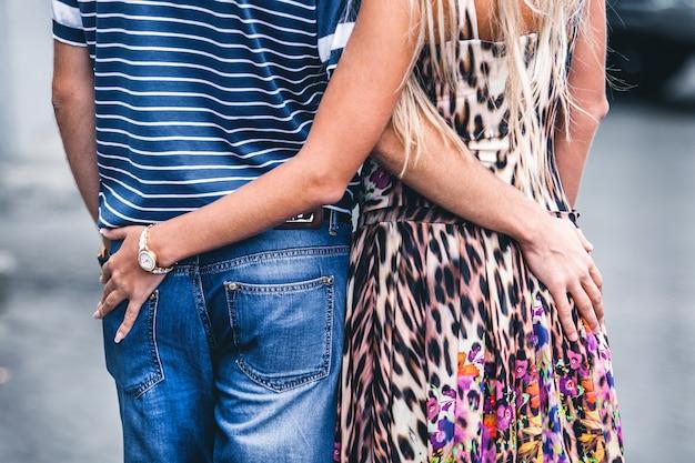 Paar houden elkaars taille vast en wandelen door de stad in de zomer