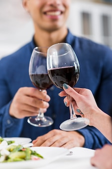 Paar houden glazen rode wijn op valentijnsdag