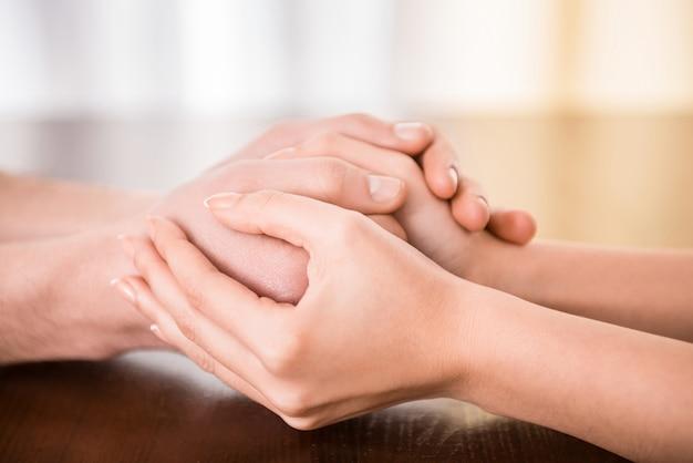 Paar houden handen op de tafel.