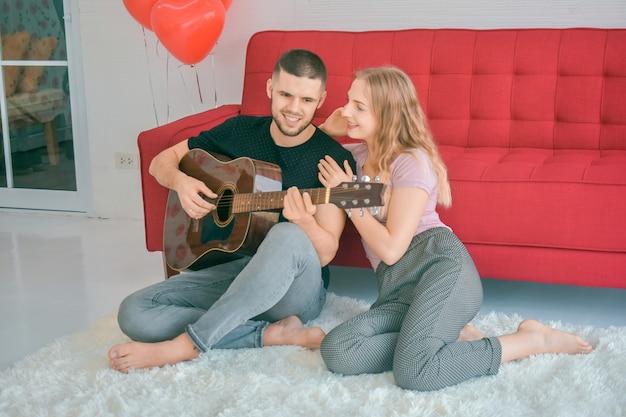 Paar houden van gitaar spelen in slaapkamer liefde in valentijnsdag concept