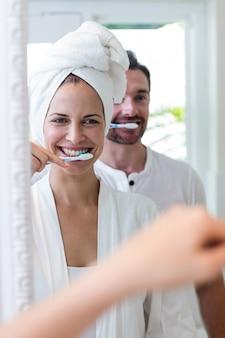 Paar hun tanden poetsen in de badkamer