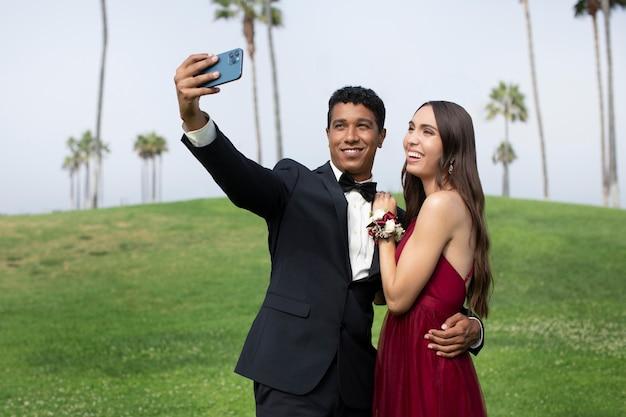 Paar in afstudeerbalkleding die een selfie maakt
