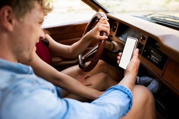 Paar in auto met smartphone close-up