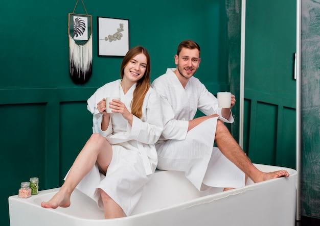 Paar in badjassen die koppen houden en in badkuip stellen