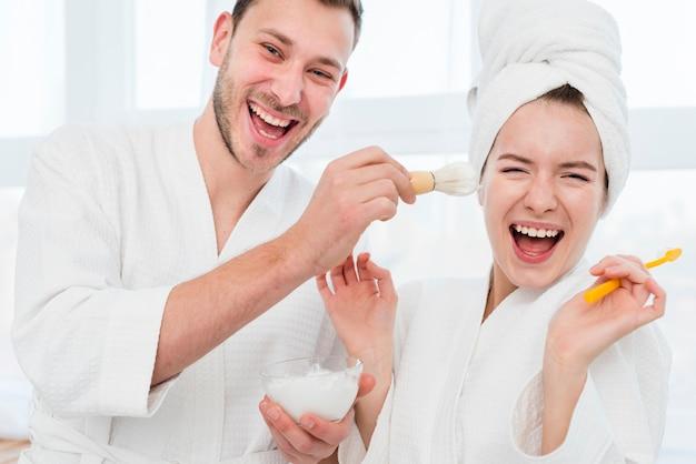 Paar in badjassen spelen met scheerschuim