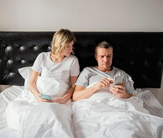 Paar in bed met behulp van mobiele telefoons