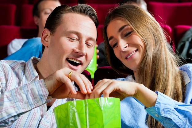 Paar in bioscoop met popcorn