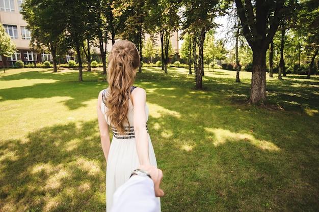 Paar in bruiloft kleding is in handen tegen de achtergrond van het veld bij zonsondergang, de bruid en bruidegom