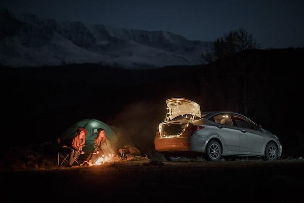 Paar in camping met kampvuur 's nachts in de bergen