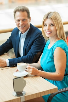 Paar in coffeeshop. bovenaanzicht van een mooi volwassen stel dat samen koffie drinkt en naar de camera kijkt terwijl ze in de coffeeshop zitten