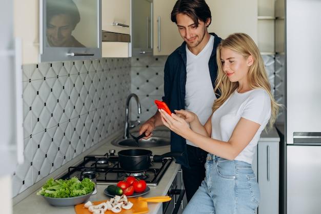 Paar in de keuken tijdens het bereiden van een gezond voedsel. - vrouw met smartphone
