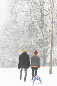 Paar in de sneeuw slepen een slee