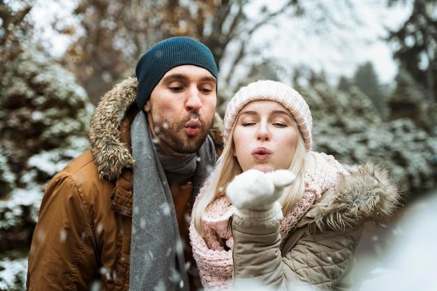 Paar in de winter waait in de sneeuw