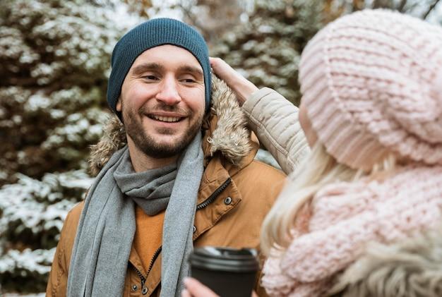 Paar in de wintermens die zijn vriendin bekijkt