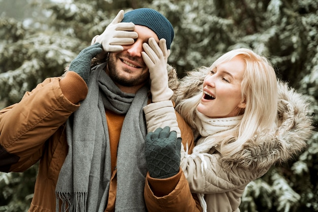 Paar in de wintervrouw die het gezicht van haar vriend behandelen