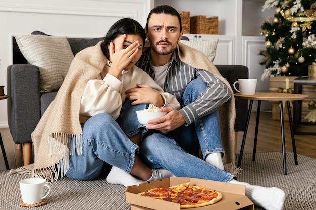 Paar in deken kijken naar een enge film
