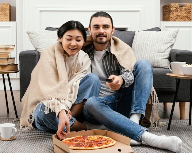 Paar in deken kijken naar een film en eten