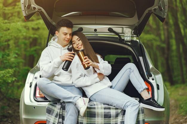 Paar in een bos zitten in een kofferbak