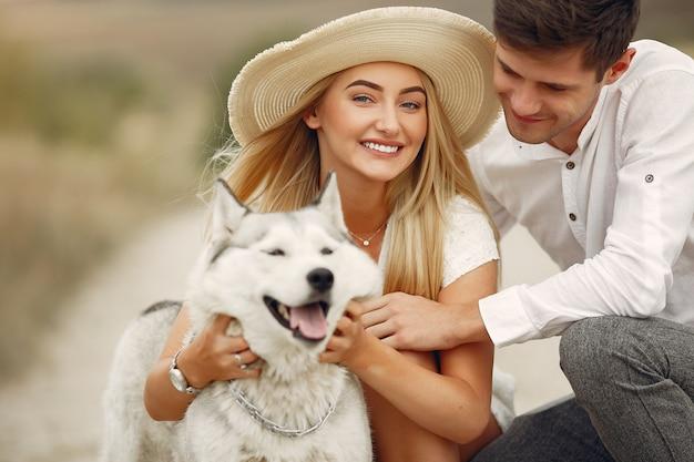 Paar in een herfst veld spelen met een hond