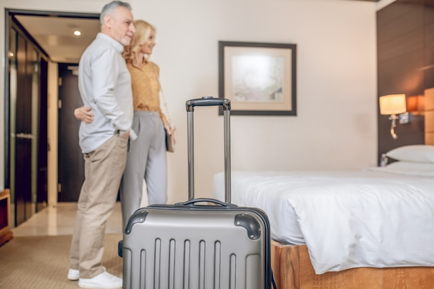 Paar in een hotel. stel van middelbare leeftijd in een hotelkamer ziet er tevreden uit