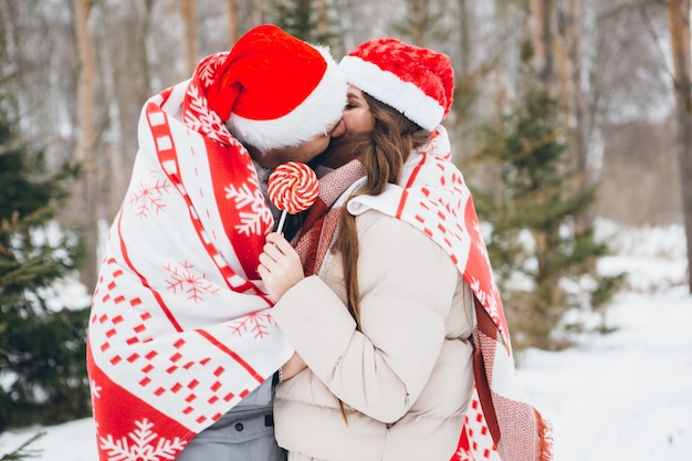 Paar in een kerstmuts en gewikkeld in een geruite knuffels en kusjes in een winter naaldbos