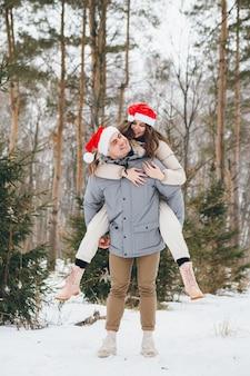 Paar in een kerstmuts en knuffelen en gek doen in een winter naaldbos