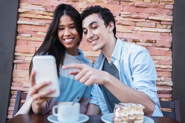 Paar in een modern café genieten van tijd samen surfen op de telefoon.