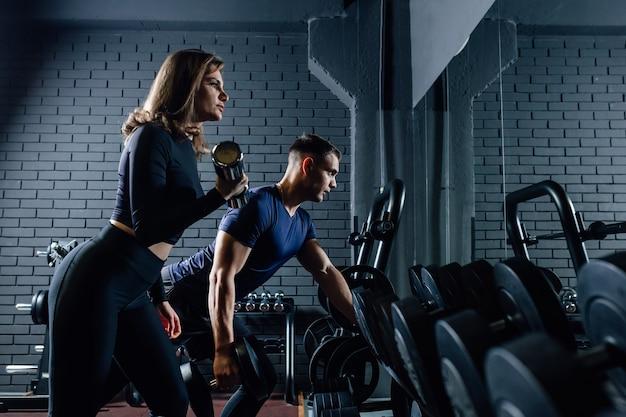 Paar in fitness gym met halters tillen gewicht als sport, man en vrouw samen trainen