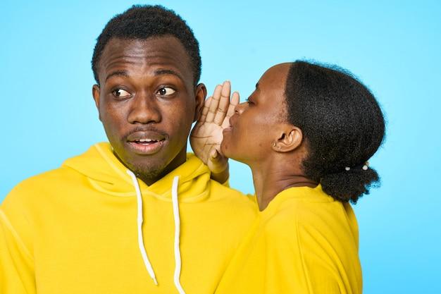 Paar in gele hoodies, meisje fluistert tegen het oor van haar vriendje