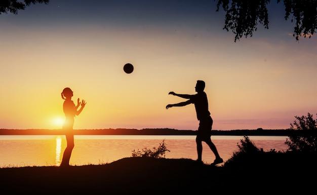 Paar in het spel bij zonsondergang aan het meer