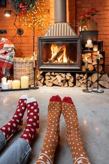 Paar in kerstsokken bij de open haard thuis. het concept van comfort tijdens winter- en nieuwjaarsvakanties