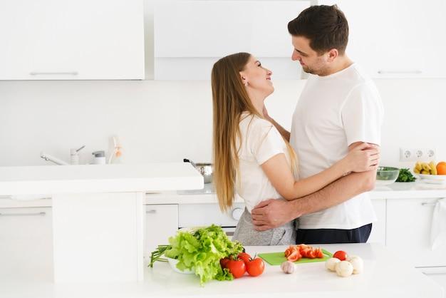 Paar in keuken knuffelen