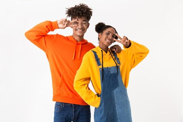 Paar in kleurrijke kleding met v-teken, geïsoleerd op een witte muur