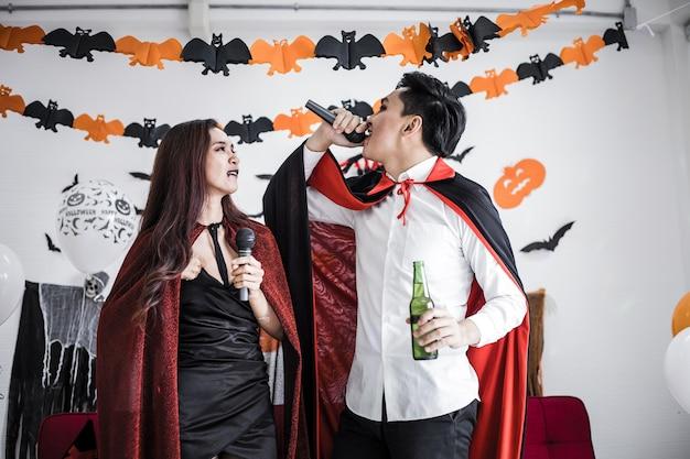Paar in kostuumheks en dracula met vieren halloween-feest en drinken bier terwijl ze samen zingen.