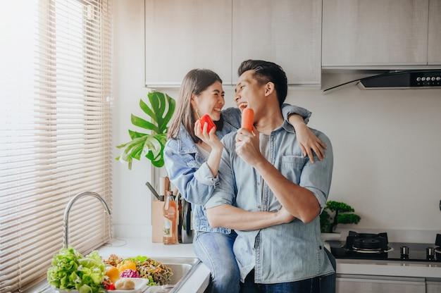 Paar in liefde die en pret met groenten in keuken glimlachen hebben